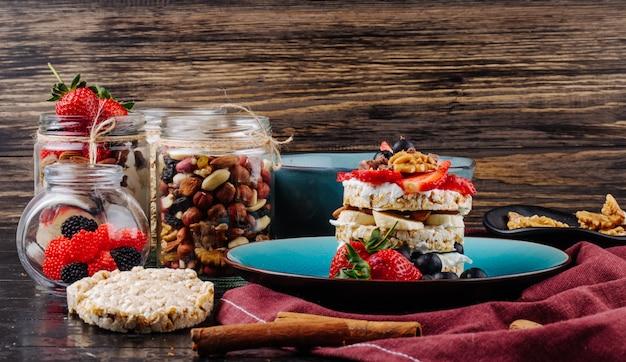 Zijaanzicht van lekkere knäckebröd met rijpe bosbessen aardbeien en noten met zure room op een keramische plaat Gratis Foto