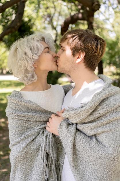 Zijaanzicht van leuk paar bedekt met deken buiten kussen Gratis Foto