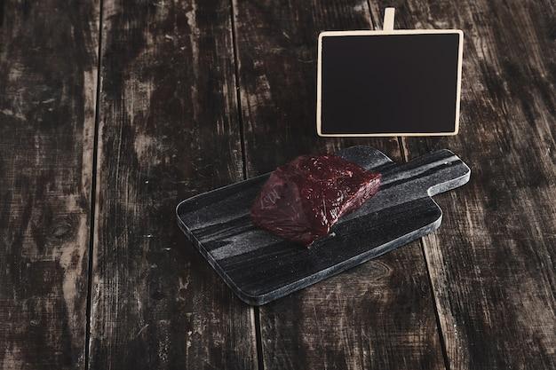 Zijaanzicht van luxe rauw stuk walvis vlees biefstuk op zwart marmeren stenen snijbureau en leeftijd vintage houten tafel en krijt bord prijskaartje Gratis Foto