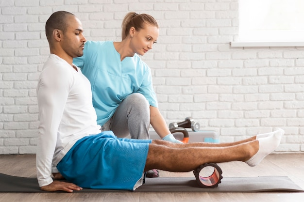 Zijaanzicht van man en fysiotherapeut die oefeningen doen Premium Foto