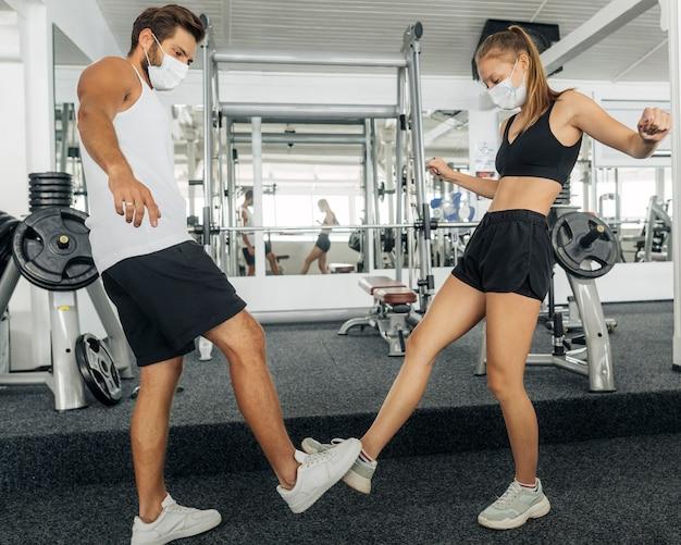 Zijaanzicht van man en vrouw die met voeten op de gymnastiek groeten Gratis Foto