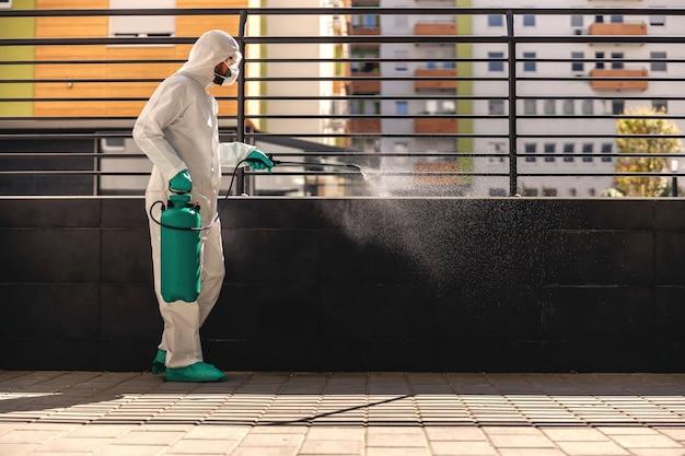 Zijaanzicht van man in steriel beschermend uniform met rubberen handschoenen die sproeier met desinfectiemiddel vasthoudt en buitenshuis sproeit om verspreiding van het coronavirus te voorkomen. Premium Foto