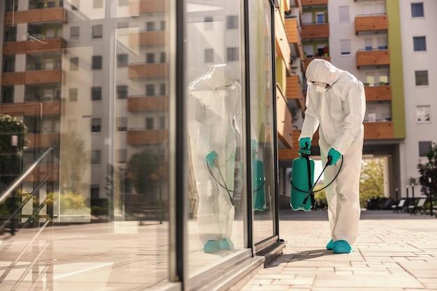 Zijaanzicht van man in steriel beschermend uniform met rubberen handschoenen die sproeier met desinfectiemiddel vasthoudt en buitenshuis sproeit om verspreiding van het coronavirus te voorkomen Premium Foto