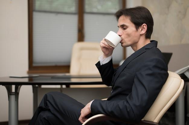 Zijaanzicht van man koffie drinken Gratis Foto