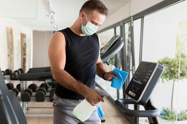 Zijaanzicht van man met medisch masker fitnessapparatuur desinfecteren Gratis Foto