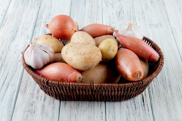 Zijaanzicht van mandhoogtepunt van groenten als ui van de knoflookaardappel op houten achtergrond Gratis Foto