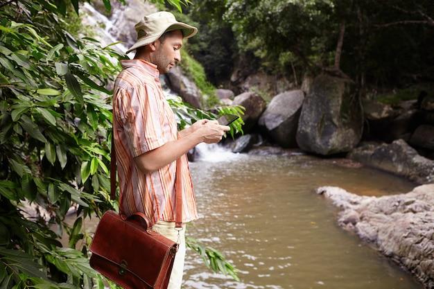 Zijaanzicht van mannelijke bioloog met leerzak op veldwerk uitvoeren van wateranalyse staande op bergrivier en fotograferen met behulp van digitale tablet met waterval en rotsen Gratis Foto