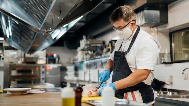 Zijaanzicht van mannelijke chef-kok met masker scherpe kip Gratis Foto