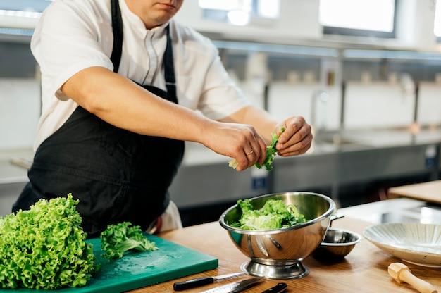 Zijaanzicht van mannelijke chef-kok scheuren salade in kom Premium Foto