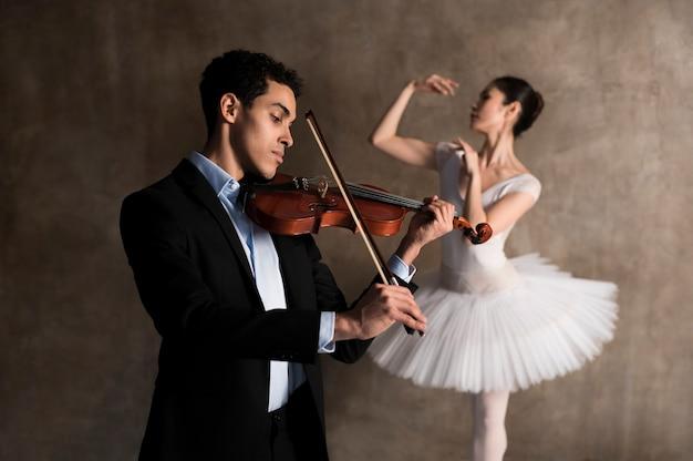 Zijaanzicht van mannelijke muzikant en ballerina Gratis Foto