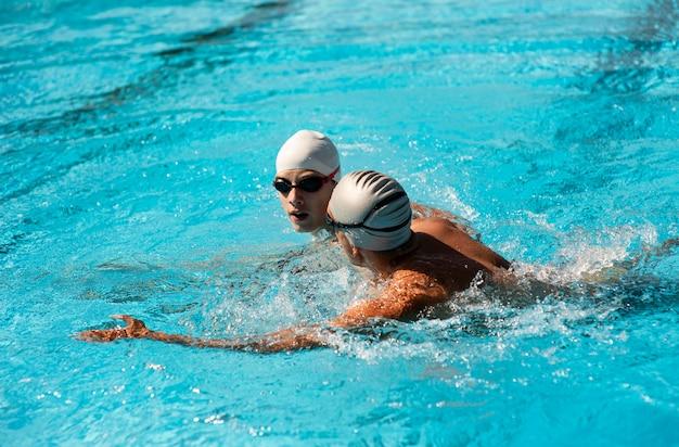 Zijaanzicht van mannelijke zwemmers die in het zwembad zwemmen Gratis Foto