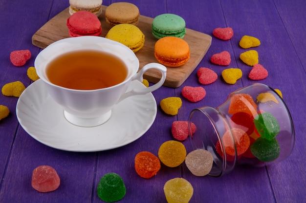 Zijaanzicht van marmelads morsen uit pot en kopje thee op schotel met sandwiches cookie op snijplank en paarse achtergrond Gratis Foto