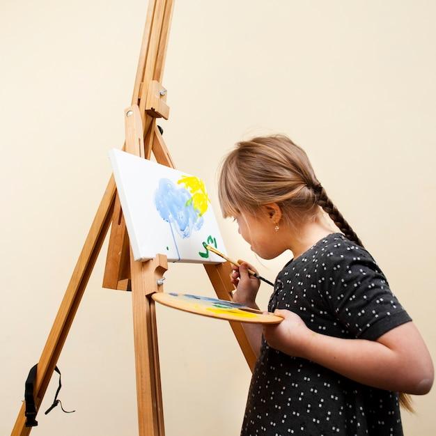 Zijaanzicht van meisje met het syndroom van down schilderen met borstel Gratis Foto