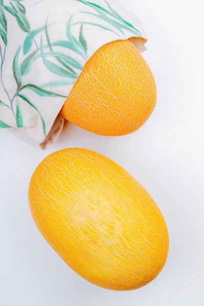 Zijaanzicht van meloenen in zak en op een witte achtergrond Gratis Foto