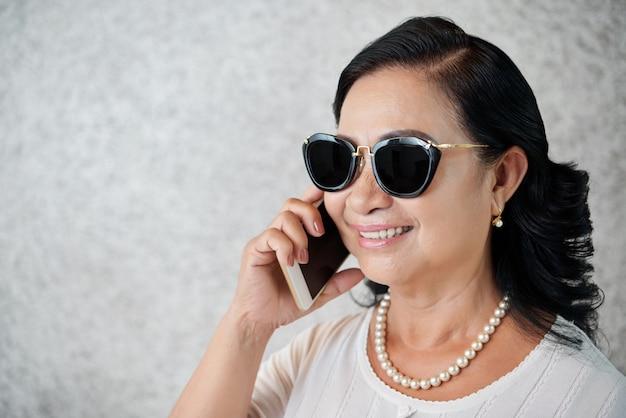 Zijaanzicht van modieuze vrouw van middelbare leeftijd praten aan de telefoon Gratis Foto