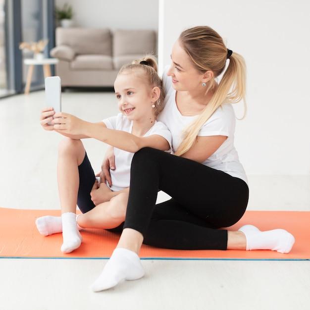 Zijaanzicht van moeder en dochter die selfie op yogamat nemen Gratis Foto