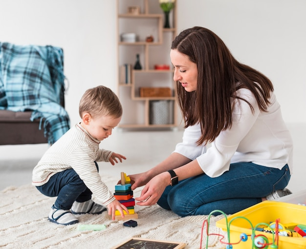 Zijaanzicht van moeder en kind spelen met speelgoed Gratis Foto
