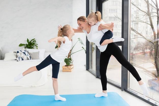 Zijaanzicht van moeder het beoefenen van yoga met dochters Gratis Foto