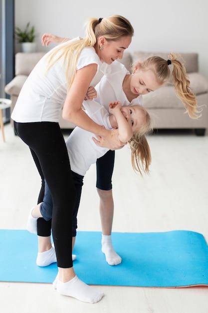 Zijaanzicht van moeder het spelen met dochters thuis terwijl het uitwerken Gratis Foto