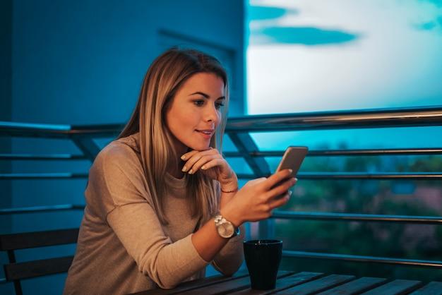 Zijaanzicht van mooie vrouw die smartphone gebruiken bij terras in de avond. Premium Foto