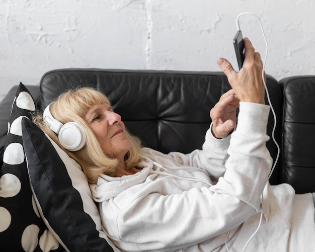 Zijaanzicht van oudere vrouw, luisteren naar muziek thuis op de koptelefoon Gratis Foto