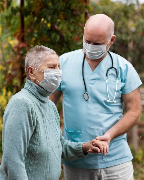 Zijaanzicht van oudere vrouw met medisch masker en verpleger Gratis Foto
