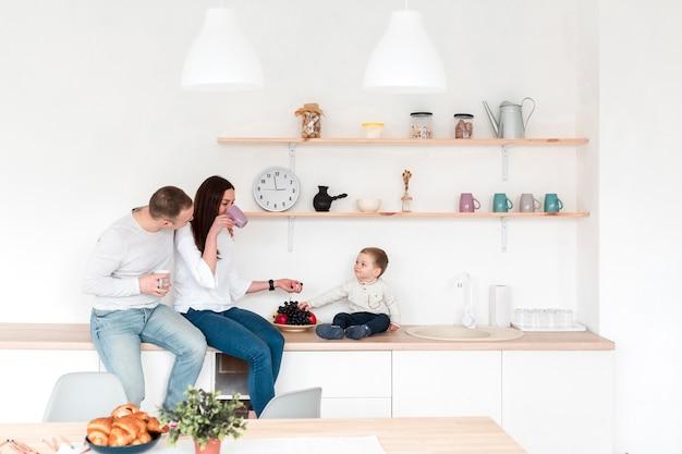 Zijaanzicht van ouders met baby in de keuken Gratis Foto