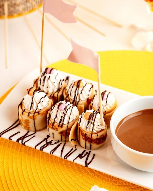 Zijaanzicht van pannenkoek rollen met slagroom en chocolade op geel Gratis Foto