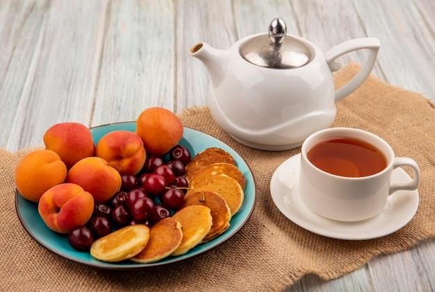 Zijaanzicht van pannenkoeken met kersen en abrikozen in plaat en kopje thee met theepot op zak en houten achtergrond Gratis Foto
