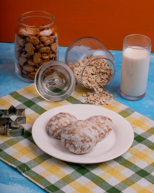 Zijaanzicht van peperkoek cookies op een witte plaat en een stervormige cookie cutter op de keukentafel Gratis Foto