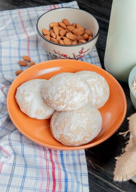Zijaanzicht van peperkoek in plaat met amandelen op plaid doek en zure geklonterde melk op houten oppervlak Gratis Foto