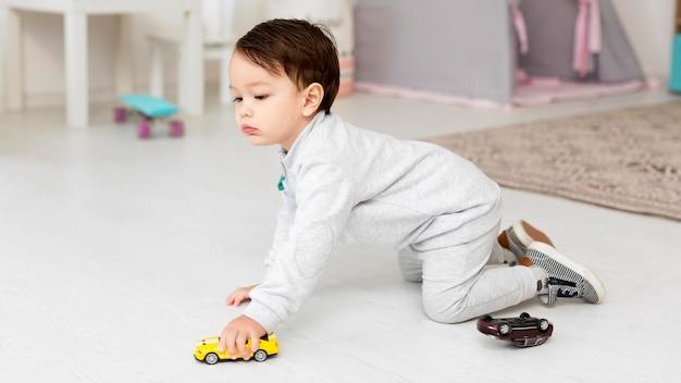 Zijaanzicht van peuter spelen met speelgoedauto Gratis Foto