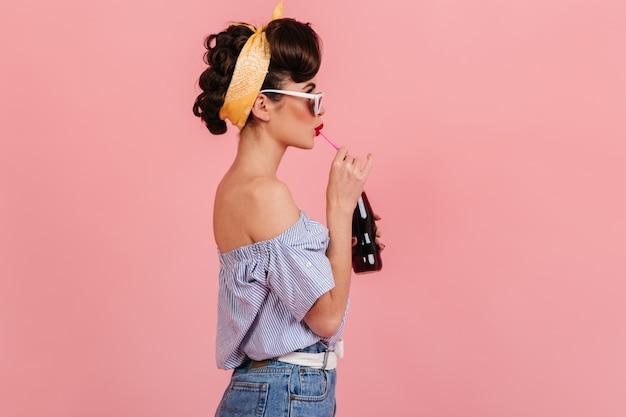 Zijaanzicht van pinup brunette meisje frisdrank drinken. studio shot van stijlvolle jonge vrouw in vintage outfit geïsoleerd op roze achtergrond. Gratis Foto
