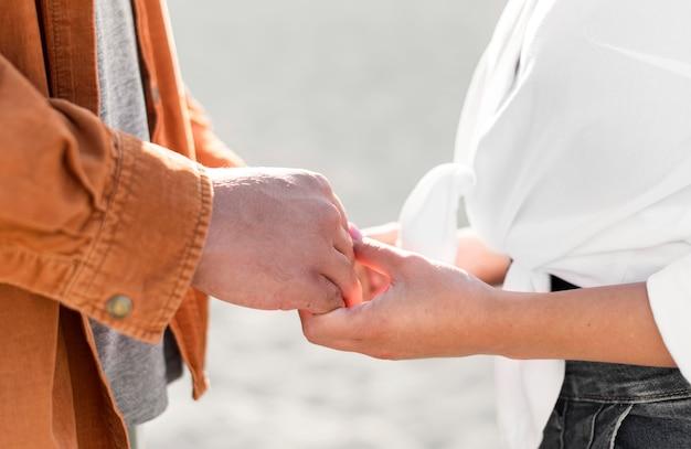 Zijaanzicht van romantisch paar hand in hand buitenshuis Gratis Foto