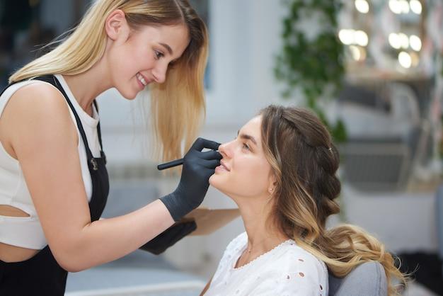 Zijaanzicht van schoonheidsspecialist die gezicht van cliënt in schoonheidssalon de contouren aangeven Premium Foto