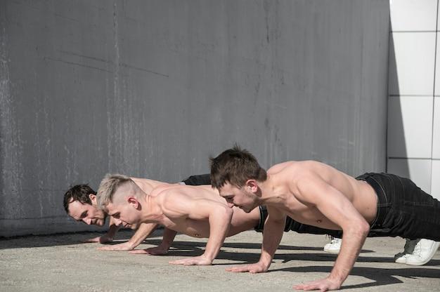 Zijaanzicht van shirtless hiphopdansers die buiten repeteren Gratis Foto