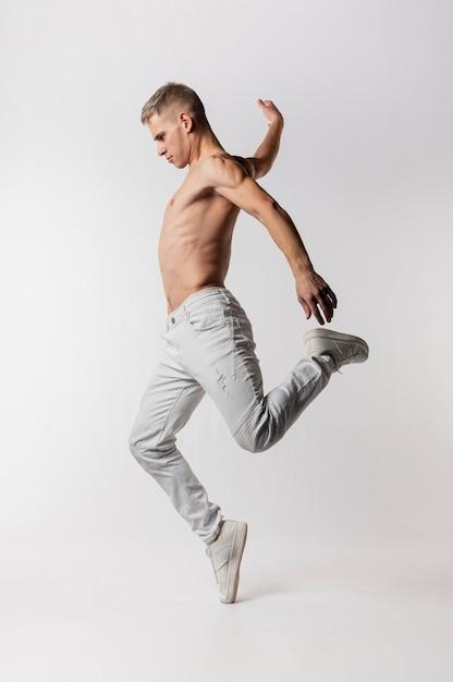 Zijaanzicht van shirtless mannelijke danser in jeans en tennisschoenen het dansen Premium Foto