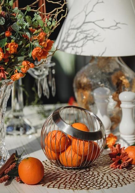 Zijaanzicht van sinaasappelen in metalen mand vaas op tafel Gratis Foto