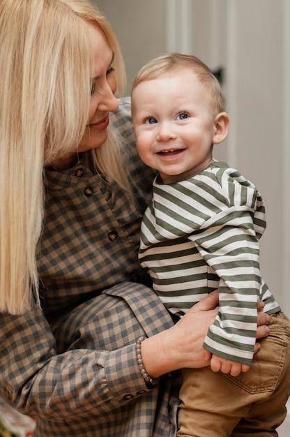 Zijaanzicht van smileygrootmoeder die haar leuke kleinzoon houdt Gratis Foto