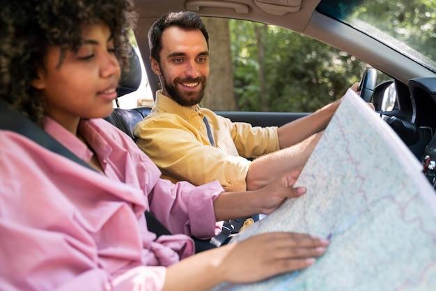 Zijaanzicht van smileypaar in auto raadplegingskaart Gratis Foto