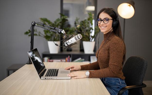 Zijaanzicht van smileyvrouw op de radio met microfoon en laptop Gratis Foto