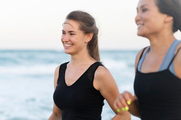 Zijaanzicht van smileyvrouwen die op het strand uitoefenen Gratis Foto