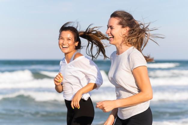 Zijaanzicht van smileyvrouwen die samen op het strand lopen Gratis Foto