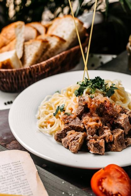 Zijaanzicht van spaghetti met stukjes vlees en tomaat op een houten bord Gratis Foto