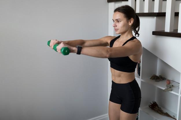 Zijaanzicht van sportieve vrouw die gewichten met exemplaarruimte gebruikt Gratis Foto