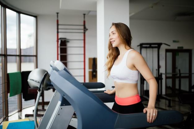 Zijaanzicht van sportieve vrouw uitoefenen op loopband in de sportschool Gratis Foto