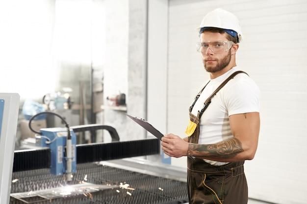 Zijaanzicht van sterke monteur in beschermende bril werken Gratis Foto