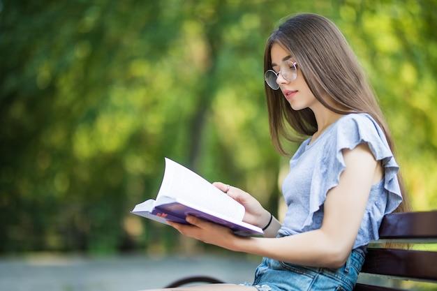 Zijaanzicht van tevreden brunette vrouw in bril zittend op een bankje en leesboek in park Gratis Foto
