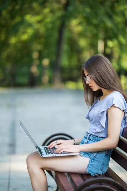 Zijaanzicht van tevreden brunette vrouw in bril zittend op een bankje in het park en met behulp van laptopcomputer Gratis Foto