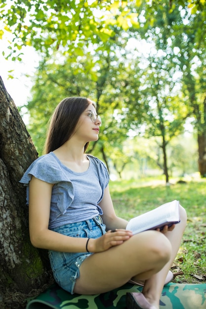 Zijaanzicht van tevreden brunette vrouw in bril zittend op het gras onder de boom en leesboek in park Gratis Foto
